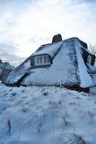 Snow covered thatched roof Royalty Free Stock Photography