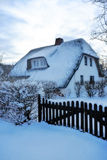 Snow covered thatched roof Royalty Free Stock Photos