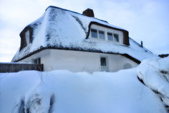 Snow covered thatched roof Stock Images