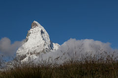 Snow covered top of Matterhorn mountain in deep blue sky with me Stock Photos