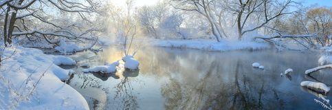 Frosty foggy winter landscape with flowing river. royalty free stock photography