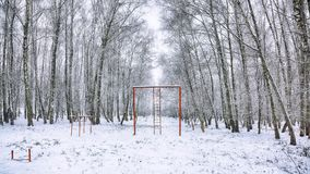 Snow-covered trees in the city park and old red horizontal bar w. Ith stairs. Winter time Royalty Free Stock Photography