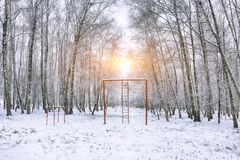 Snow-covered trees in the city park and old red horizontal bar w. Ith stairs. Sunset time Stock Photography