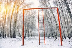 Snow-covered trees in the city park and old red horizontal bar w Royalty Free Stock Photography