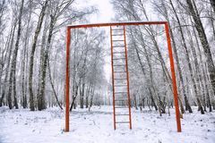 Snow-covered trees in the city park and old red horizontal bar w Royalty Free Stock Photo