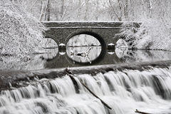 Waterfall And Bridge. Snow Covered Trees Framing A Stone Bridge And Waterfall During Winter In The Park, Sharon Woods, Southwestern Ohio, USA Stock Photo