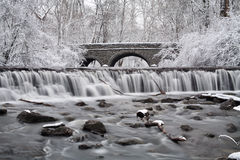 Waterfall And Bridge. Snow Covered Trees Framing A Stone Bridge And Waterfall During Winter In The Park, Sharon Woods, Southwestern Ohio, USA Royalty Free Stock Image