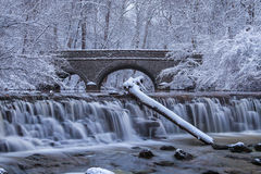 Snow Covered Trees. Framing A Stone Bridge And Waterfall During Winter In The Park, Sharon Woods, Southwestern Ohio, USA Royalty Free Stock Photography