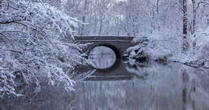 Snow Covered Trees and Stone Bridge. Snow covered trees framing a stone bridge reflected in the mirror - like river water during winter In the park, Sharon Woods Stock Photos