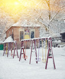 Snow-covered trees and swings in the city park Royalty Free Stock Photography