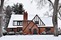 Snow Covered Tudor House with Christmas Wreath. Residential Tudor Revival home during winter. Snow covered roof, blue arched door, brick exterior, oriel window stock photo