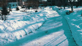 Snow covered walkway of park. Winter snow-covered path in the park. Benches in the snow trees in the snow, snow shimmers in the sun stock footage