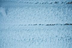 Snow-covered wall of the hut. Wooden boards covered with snow. Icy house Stock Image
