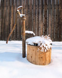 Snow Covered Water Well. Stack of cut firewood covered in a layer of white fluffy snow stock photos