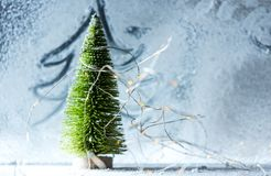 Christmas time background - Snow-covered window with green, symbolic tree and lights stock image