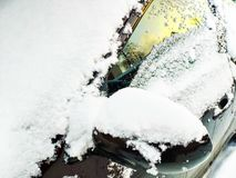 Snow-covered windshield, side window and left rear-view mirror stock photography