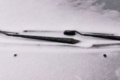 Snow covered windshield with wiper blades. Concept of driving in winter time with snow on road. Winter season stock photography