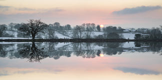 Snow covered Winter countryside sunrise landscape reflected in s Stock Photos