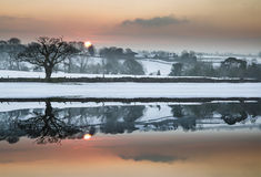 Snow covered Winter countryside sunrise landscape reflected in s Stock Photography