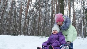 In the snow-covered winter forest, two girls, one year and seven years old, have fun sledding. the elder sister rolls. The younger sister on the sled stock video