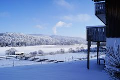 Snow-covered winter landscape with part of the balcony, mountains and forests and fields in the snow. Photo stock images