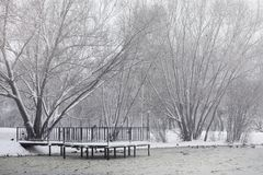 Snow-covered winter park and benches. Park and pier for feeding. Ducks and pigeons. The snow covered the autumn park.r Stock Photos
