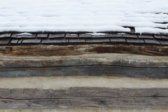 Snow Covered Wood Shingles on a Log Barn Royalty Free Stock Photography