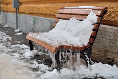 Snow-covered wooden bench with icicles. SAINT-PETERSBURG, RUSSIA - NOVEMBER 15, 2016: Snow-covered wooden bench with icicles stock photos