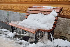 Snow-covered wooden bench with icicles. SAINT-PETERSBURG, RUSSIA - NOVEMBER 15, 2016: Snow-covered wooden bench with icicles stock images