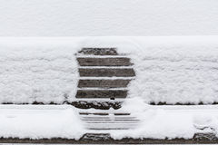 Snow-covered wooden bench with an imprint of someone Royalty Free Stock Image