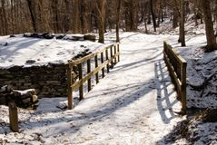 Snow Covered Wooden Bridge on a Walking Trail Royalty Free Stock Photography