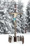 Snow covered wooden cross with Jesus Stock Photos