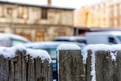 Snow-covered wooden fence on a blurred city background - image.  royalty free stock image