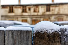 Snow-covered wooden fence on a blurred city background - image.  stock photos