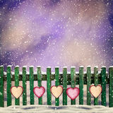 Snow-covered wooden fence with hanging on it with paper hearts Stock Images