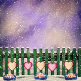 Snow-covered wooden fence with hanging on it with paper hearts a Stock Photos
