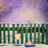 Snow-covered wooden fence with a paper heart and a gift Stock Photos