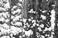 Snow-covered wooden fence. The site of the wooden fence is covered with snow lumps royalty free stock images