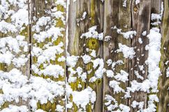 Snow-covered wooden fence. The site of the wooden fence is covered with snow lumps stock photos
