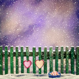 Snow-covered wooden fence with two paper hearts Stock Photo