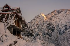 Snow covered wooden house in mountains - Majestic winter landscape in himalayas. Snow covered wooden house in mountains - Majestic winter landscape in himalaya royalty free stock photo