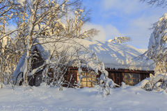 Snow-covered wooden hut Stock Images