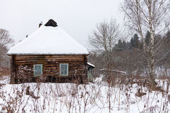 Snow covered wooden rustic house Stock Images
