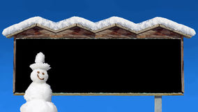 Snow covered wooden signboard against blue sky and snowman Royalty Free Stock Photography