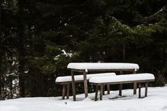 Snow covered wooden table and benches in forest. Vacant snow covered wooden table and benches in winter snow in a park. Recreation picnic area Royalty Free Stock Image