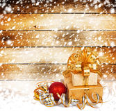Snow-covered wooden wall with a beautiful gift box Royalty Free Stock Image