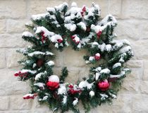 Snow Covered Wreath. Christmas wreath with snow on top of it with a brick background Royalty Free Stock Images