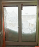 Snow covers half window. Snowfall in Europe royalty free stock photos