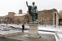 Snow covers the streets of Rome, Italy. Statue of Nerva. stock photo