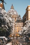 St. Peter`s Snow. Snow covers the trees along a street approaching St. Peter`s Basilica in the Vatican Royalty Free Stock Photo